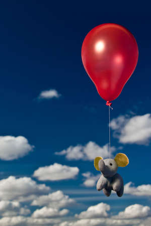 An elephant flying with a red ballon