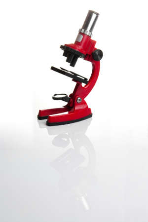 Side view of a red microscope isolated on white background with reflection Stock Photo