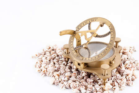 Old nautical sundial compass with shells isolated in a white background