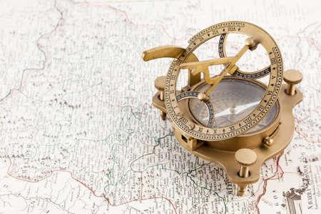 reloj de sol: Antiguo reloj de sol, compás náutico sobre un mapa antiguo Foto de archivo