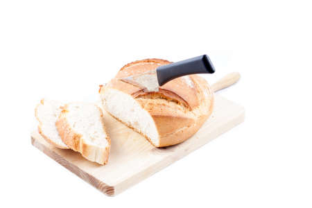 Hogaza  Spanish bread, similar to bread boule  over a kitchen cutting board isolated in a white background
