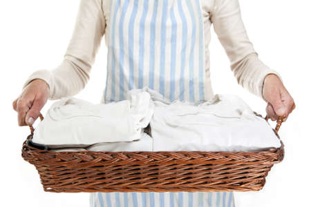 A woman is holding a basket of clothes to iron, isolated photo