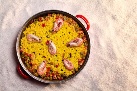Typical spanish paella over the sand of the beach photo