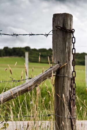 cerca blanca: Una valla de cerca de una carretera en un d�a muy nublado