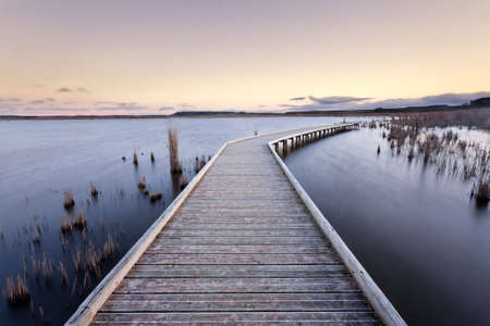 A gangway over a lake during the sunset. Lake of Pitillas, Navarra (Spain).  Stock Photo