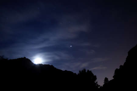 Night shot with the moon rising over the mountains Stock Photo