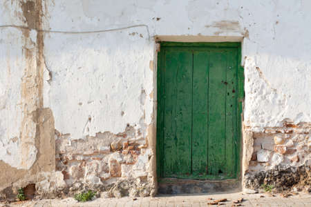 The facade of an old and rustic house, with a green door photo