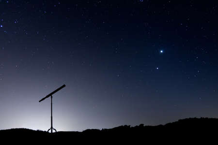 spyglass: Night shot with a silhouette of a telescope, with a sky full of stars and the conjunction of Venus and Jupiter