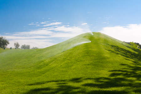 Watering green sloping meadows during summer Stock Photo