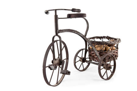 An old bike carrying a basket of nuts, isolated on a white background Stock Photo