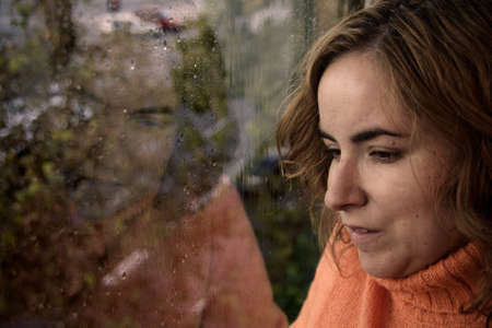 Portrait of a young woman looking through the window on a rainy day in autumn Stock Photo