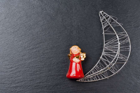 silvered: Christmas ornament  christmas angel and silvered moon with a slate stone as background Stock Photo