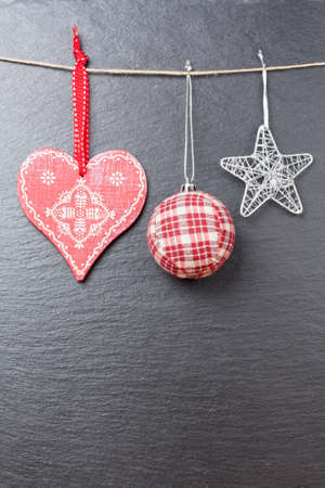 silvered: Christmas ornament  christmas ball, silvered star and a red heart with a slate stone as background