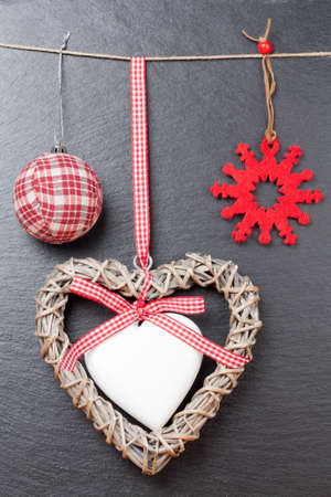 Christmas ornament  christmas ball, red snowflake and a wooden heart with a slate stone as background photo