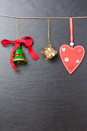 Christmas ornament  green bell, golden drum and red heart with a slate stone as background photo