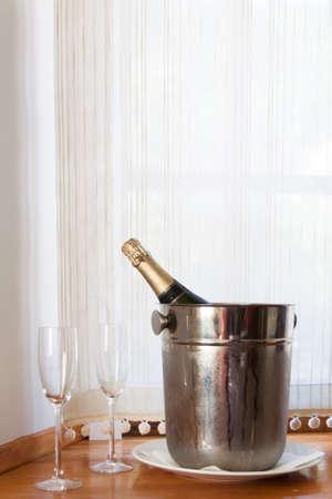 Botella de Champagne en cubo de hielo y dos vasos de champán en el alféizar de la ventana