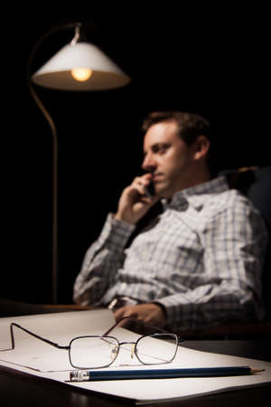 A notebook, a pencil and glasses in the foreground, with a man speaking by phone sitting in a chair in a dark room