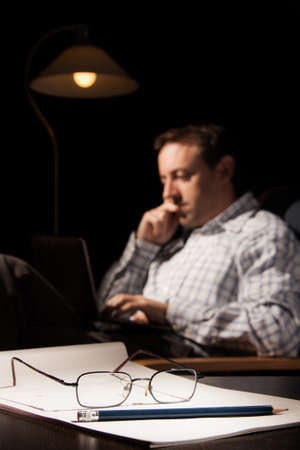 A notebook, a pencil and glasses in the foreground, with a man with a laptop sitting in a chair in a dark room Stock Photo
