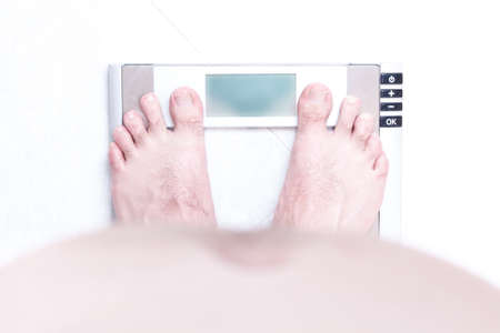 Man with overweight and big belly standing on bathroom scales Stock Photo