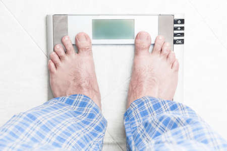 weigh: Healthy young man standing on bathroom scale