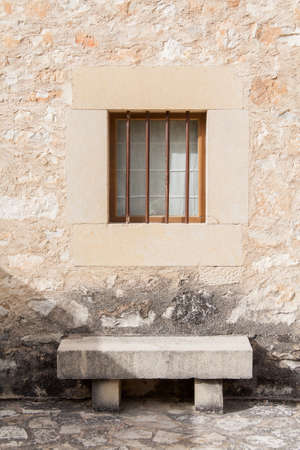 A stone bench under a window in a stone block wall of a traditional house in village of Pedraza, Spain