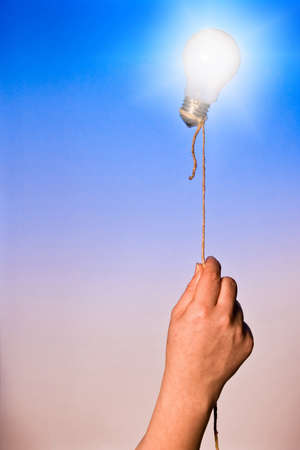 A light bulb floating attached by a rope photo