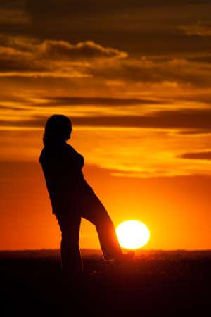 mujer mirando el horizonte: Silueta de una mujer contra el cielo en la puesta de sol con el sol con el pie