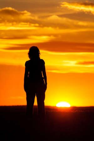 mujer mirando el horizonte: Silueta de una mujer contra el cielo al atardecer