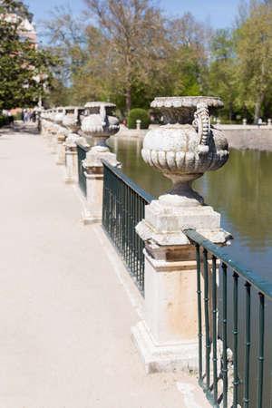 Stone jars over a railing near a river