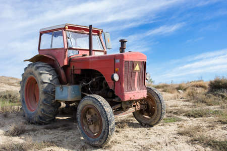 Old red tractor in the field with a cloudy sky Stock Photo