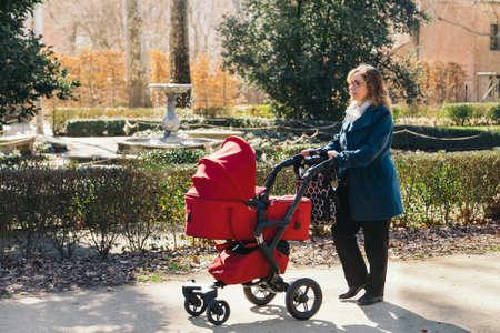 niño empujando: Madre que recorre con el cochecito de bebé en el parque