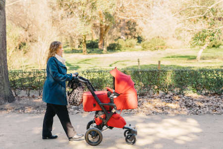 Mother walking with baby stroller in park Stock Photo