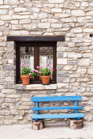 Flowery window and blue bench in a village in Spain