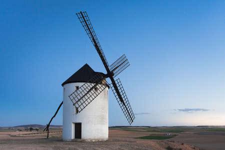 Molino de viento típico con la luna al fondo en Castilla la Mancha, España Foto de archivo