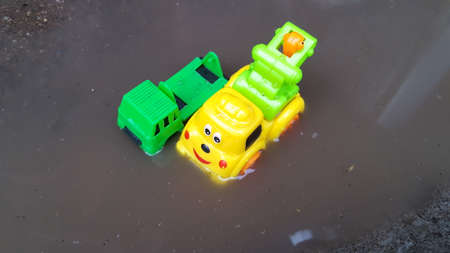 Toy tow trucks that are submerged in water, illustrate the flood conditions