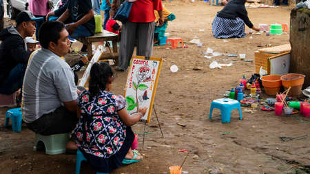 Ponorogo, Indonesia- 01012020: Parents who are accompanying their children learn to draw in an open space. Early talent development is important in parenting