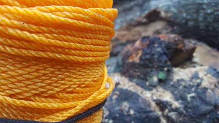 Yellow rope pile closeup photo. Ship or rock climbing tackle. Natural material woven cordage. Simple rope bulk concept. Alpine mountaineering equipment. Safety rope texture. Yacht tackle bundle card Stock Photo