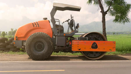 Vibration single-cylinder road roller leveling the ground for the foundation. Soil Compactor for laying asphalt on road at construction site. Road compaction equipment