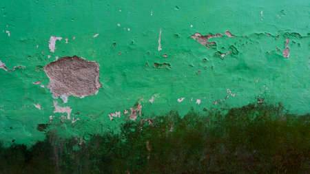 Green color wall with cracks in several parts, the picture is suitable to be used as a background image, wallpaper, or graphic resource