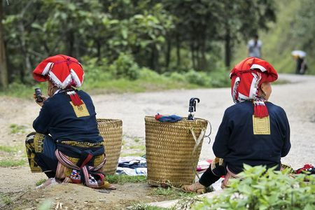 Two hill tribe women waiting by the roadside with mobile phone, Vietnam