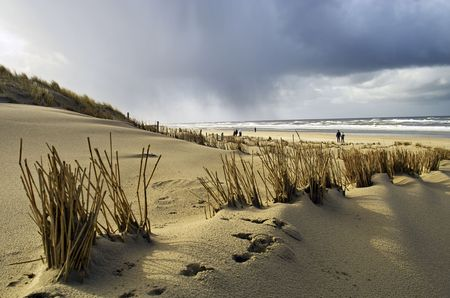 People walking on the beach on a winters day in Holland Stock Photo