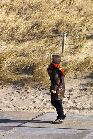 Woman walking to the beach on a windy winters day photo