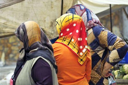 Three Turkish women in a market wearing headscarfs