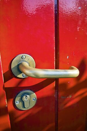 Close-up of a door handle on a bright red door Stock Photo