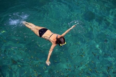 A woman snorkeling in the sea surrounded by fish photo