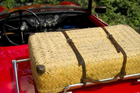 Wicker picnic basket on rear of a red vintage auto