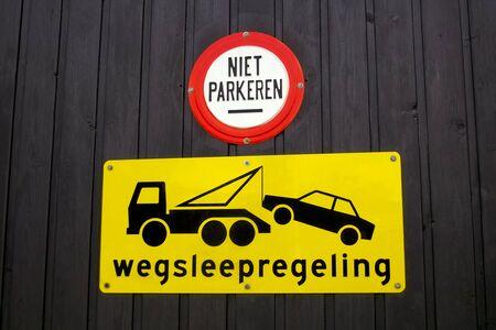 Tow away sign on a garage door in Dutch photo