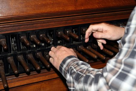 Man playing a carillon, set of bells in a tower, played using a keyboard or by an automatic mechanism similar to a piano roll