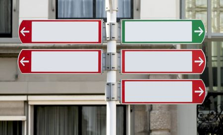 Four red and one green directional sign post, pointing to the left and right with buildings in the background