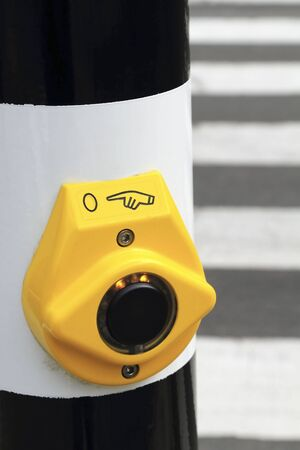 Close up shot of a yellow crosswalk button with a blurred road in the background photo